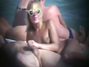 Sexy blonde gives handjob at public beach